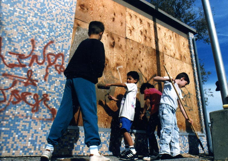 Students remove graffiti on a local building.